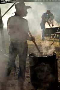 Stirring the beans in a 50 gallon cast-iron wash pot in Millheim, TX at a community BBQ